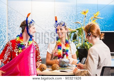 Man and woman booking beach holiday in travel agency wearing their vacation outfit