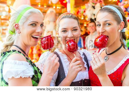 Friends visiting together Bavarian fair in national costume eating candy apple