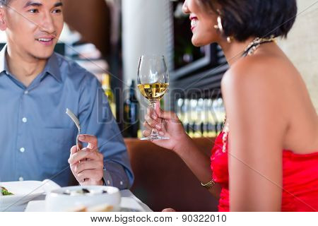 Asian couple having dinner and drinking red wine in very fancy restaurant