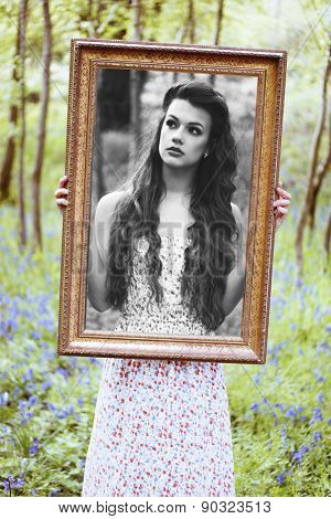 Ravishing beautiful redhead long haired woman wearing a low-cut sleeveless dress with floral pattern while looking at camera through a brown handheld portrait frame in a deciduous forest