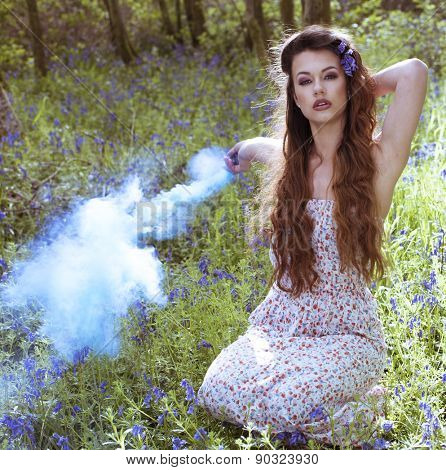Artistic portrait of a girl in a bluebell forest surrounded by smoke