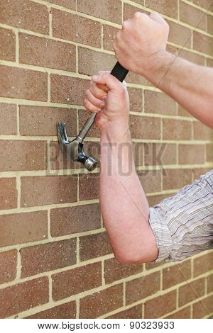 Man hitting an exterior face brick wall with a metal claw hammer in a conceptual image, close up of his hand