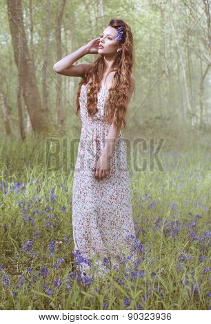 Artistic portrait of a girl in a bluebell forest wearing long dress