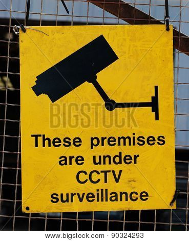 Yellow warning sign for CCTV surveillance using security cameras to secure a premises against crime on a wire mesh fence