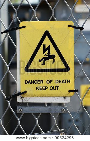 Rectangular yellow high voltage warning sign warning of the risk of death mounted on a wire mesh perimeter fence