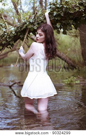 Brunette Woman Wearing Short White Sun Dress Standing Thigh Deep in Water Holding Onto Tree Branch and Looking Virginal and Seductively Back Over Shoulder