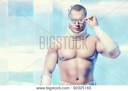 Futuristic handsome man with perfect muscular body stands on a luminous transparent background. Technology. Future concept.