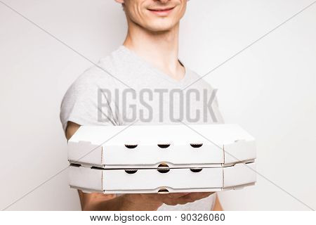 Young Man Offers Two Boxes With Pizza.
