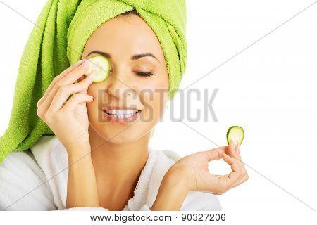 Woman in bathrobe applying cucumber on eyes.