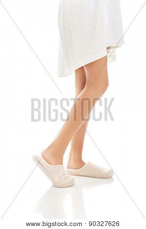 Side view of female feet in white slippers.