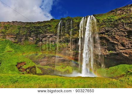 Seljalandsfoss waterfall in Iceland. Sunny day in July. Large rainbow decorates a drop of water