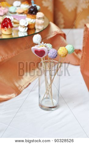 Colorful lollipops on white table. Heart and round shaped lollipops placed in a glass on table
