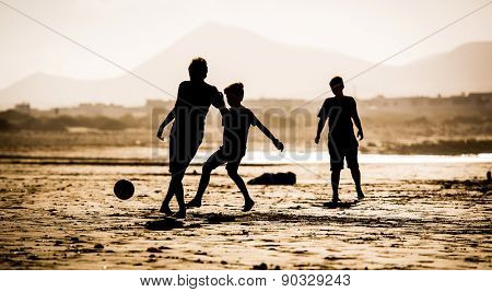 Silhouette of children on the beach with a ball