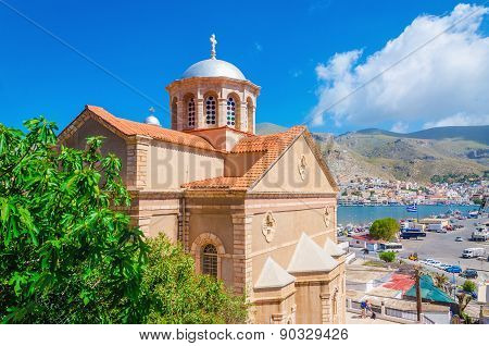 Greek church with red roof and city port