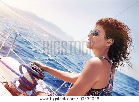 Beautiful woman working on sailboat, holding rope on crank, enjoying bright sunny day, amazing summer adventure on luxury water transport