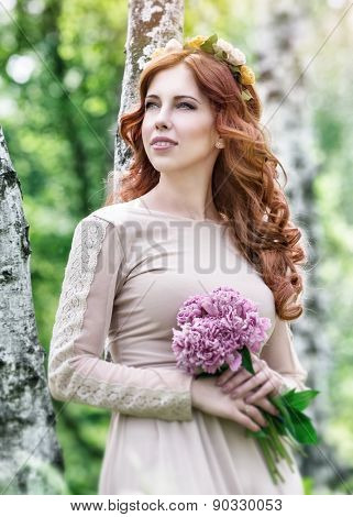 Cute dreamy bride portrait, beautiful girl standing in the park with nice pink flower bouquet in hand, gentle bridal style, fashion and tenderness concept