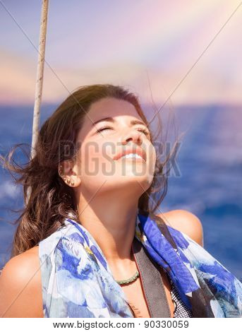 Portrait of happy girl enjoying bright sun light with closed eyes on sailboat in the sea, spending summer vacation on the beach, pleasure and happiness concept