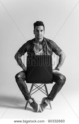 Young hipster posing at the studio, sitting on a chair