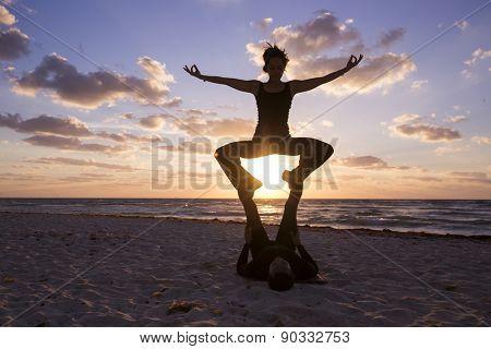 Couple practicing acroyoga at sunrise