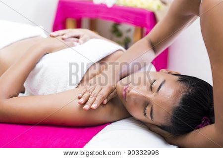 Portrait of a young woman receiving a massage