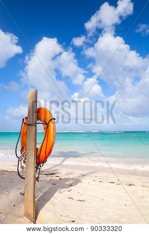 Red Life Buoy Hanging On Wooden Pole