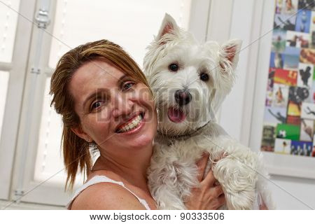 Happy Brazilian woman owner of her West Higland White Terrier dog.