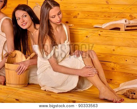 Group people relaxing in sauna. Three girls.