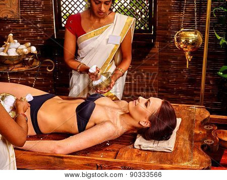 Woman having ayurvedic massage with pouch of rice. Indian girl.