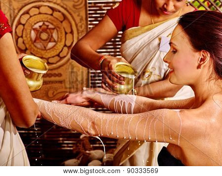 Woman having Ayurvedic spa treatment. Pouring milk. Picture on background.