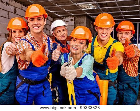 Group people in blue builder uniform thumb up. Six persons.