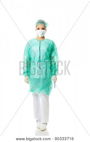 Full length female doctor with a scalpel.