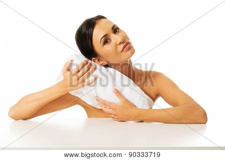 Nude woman rests her head on a rolled towel.