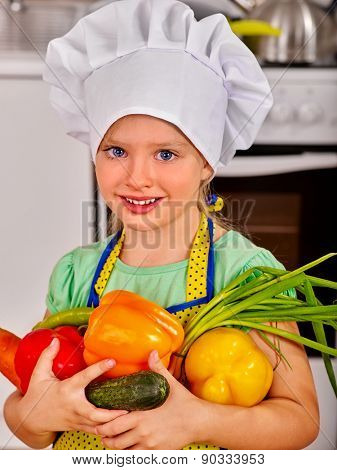 Child in cooking hat holding vegetable at kitchen.