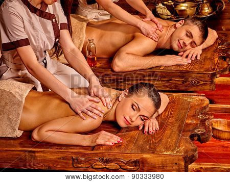 Loving couple  having oil Ayurveda spa treatment on wooden bed.