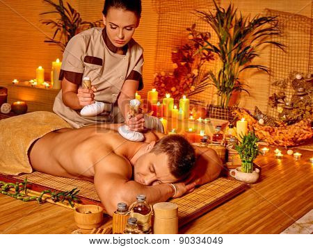 Man getting herbal ball massage in bamboo spa. Burning candels near palm tree.