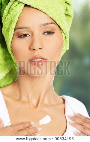 Spa woman in bathrobe with lotion on chest.