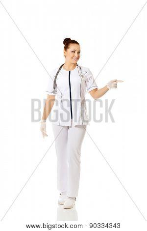 Full length female doctor pointing to the left.
