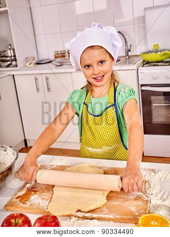 Smiling child female with rolling-pin dough at kitchen.