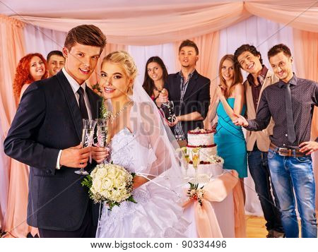 Happy wedding couple drinking champagne. Gosts background.