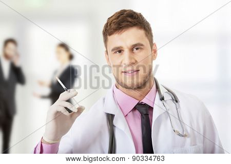 Handsome male dentist doctor holding a syringe.