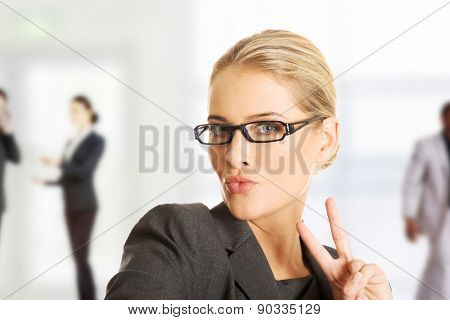 Business woman showing victory or peace sign.