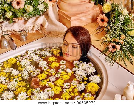 Woman applying moisturizer wild flower at bathroom.