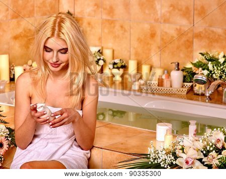 Woman applying moisturizer at bathroom near water.