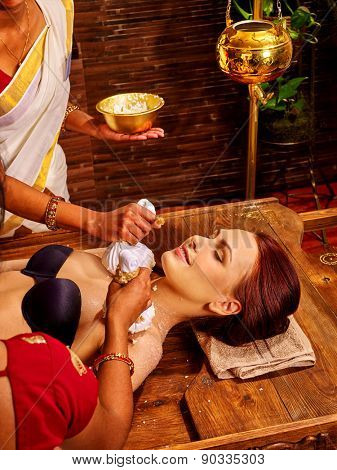 Indian woman taking ayurvedic massage with pouch of rice.