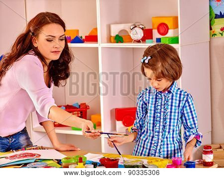 Mother with kid  painting  child picture in school. Education.