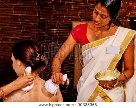 Woman having ayurvedic massage with pouch of rice. Sitting back in frame