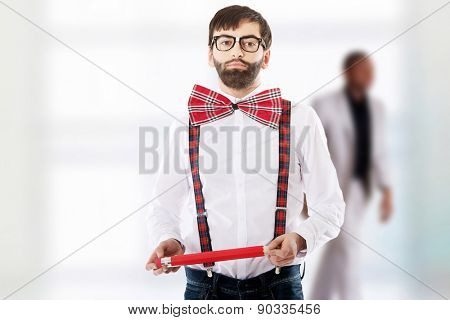 Funny man wearing suspenders pointing with big pencil.