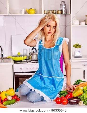 Unhappy tired woman in a blue apron preparing food at kitchen. Sitting on table.