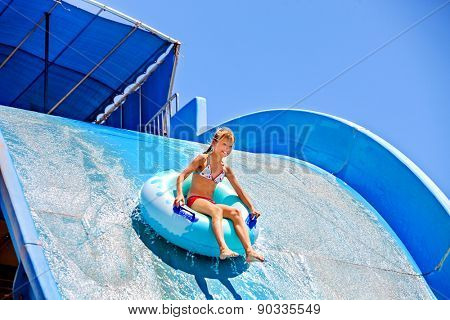 Girl slides down a very steep water slide at aquapark.