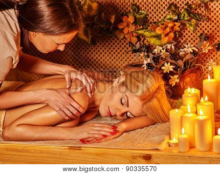 Blond woman getting massage in tropical spa. Burning candels